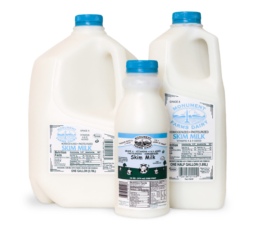 A pint, half gallon, and gallon jug of Monument Farms local skim milk.