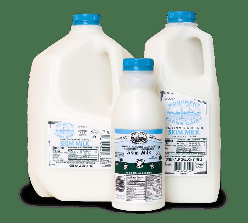 A pint, half gallon, and gallon jug of Monument Farms local skim milk.