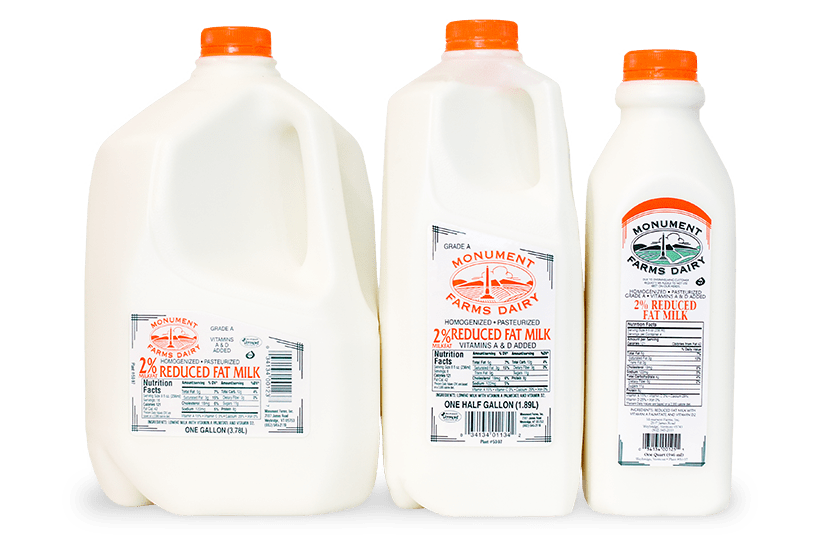 A quart, half gallon, and gallon jug of Monument Farms local 2% milk.