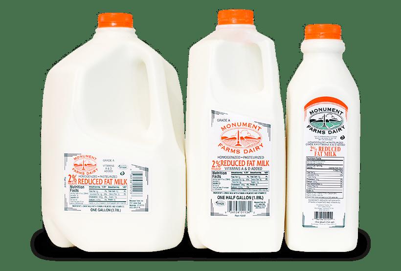 A quart, half gallon, and gallon jug of Monument Farms local 2% milk.