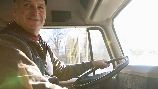 Bob James a man in his fifties with white hair, driving a truck, smiles into camera, one of the team at Monument Farms Vermont Dairy Distributor