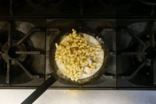 Cavatappi pasta added to sauce and tossed until evenly coated. Step eight in the Cavatappi Carbonara recipe shared by the chefs at Leunig's Bistro as one of their local Vermont recipes made with Monument fresh local heavy cream.