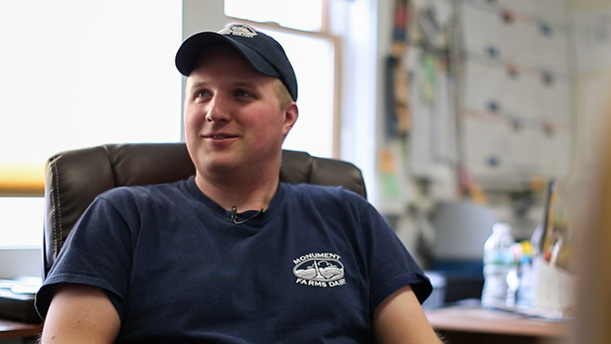 Dan James a young man in his thirties with a blonde hair and a navy blue hat smiles into camera, one of the team at Monument Farms Vermont Dairy Distributor