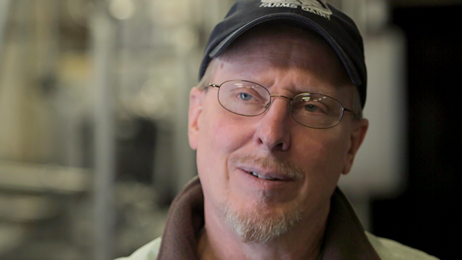 Jon Rooney a man in his fifties with a beard, glasses and hat smiles into camera, one of the team at Monument Farms Vermont Dairy Distributor