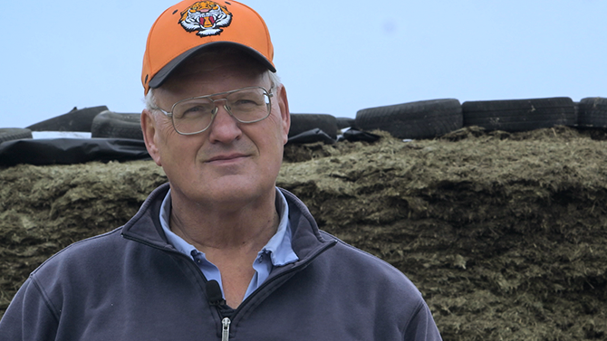 Pete James a man in his fifties with glasses and a hat smiles into camera, one of the team at Monument Farms Vermont Dairy Distributor
