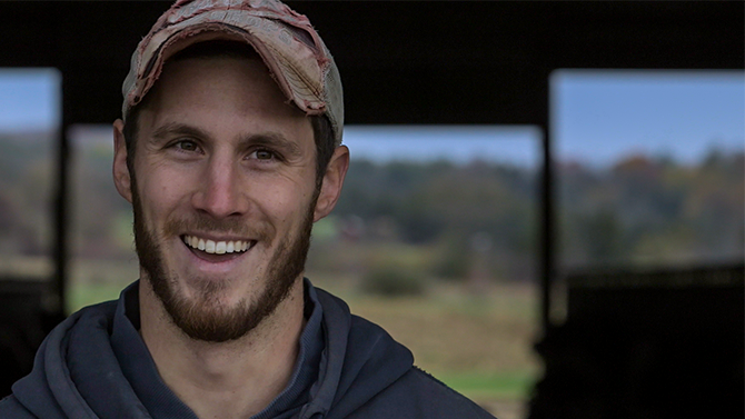 Tyler James a young man in his thirties with a beard and hat smiles into camera, one of the team at Monument Farms Vermont Dairy Distributor